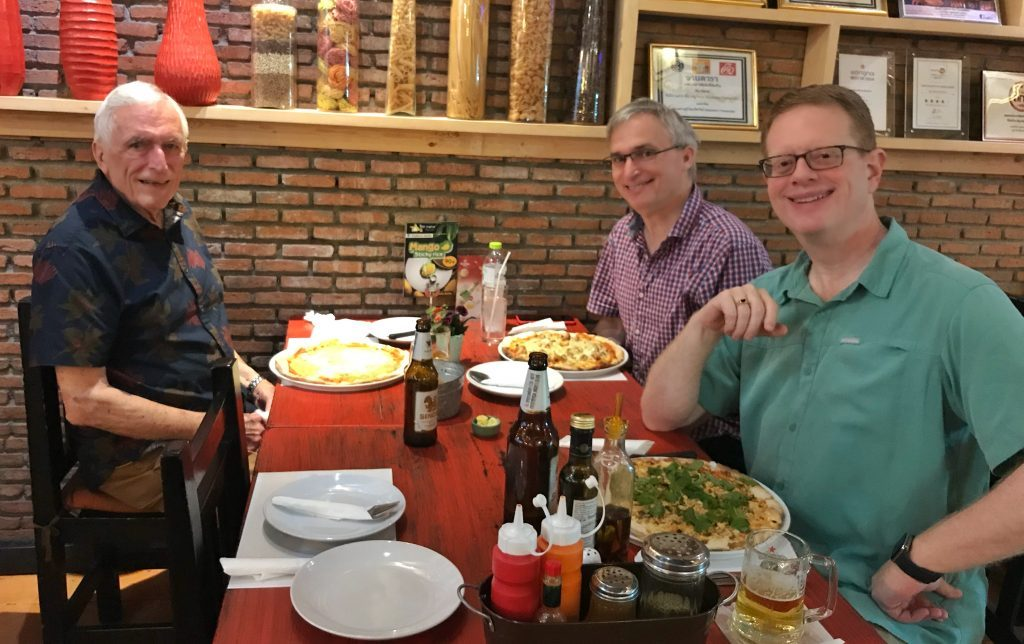 Three men sit at a table in an Italian restaurant in Bangkok, Thailand.