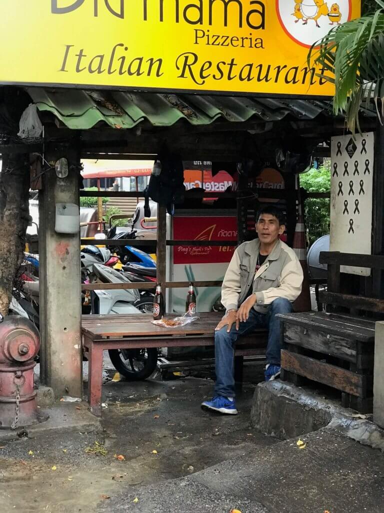 A Thai man takes a break outside a restaurant, drinking two beers and eating a plate of spicy meat.
