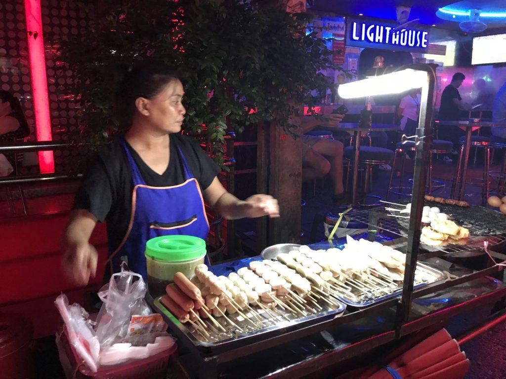 A female Thai street vendor grills meat snacks on wooden skewers.